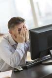 Ματαιωμένος επιχειρηματίας με τα χέρια στο πρόσωπο που εξετάζει τον υπολογιστή Στοκ Εικόνα