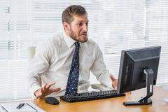 Ματαιωμένος επιχειρηματίας που εξετάζει τον υπολογιστή του Στοκ Φωτογραφίες