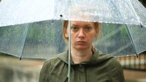 Ματαιωμένος με τον καιρό, που στέκεται κάτω από την ομπρέλα κατά τη διάρκεια της βροχής δυστυχισμένη γυναίκα απόθεμα βίντεο