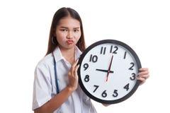 Ματαιωμένος νέος ασιατικός θηλυκός γιατρός με ένα ρολόι Στοκ εικόνες με δικαίωμα ελεύθερης χρήσης