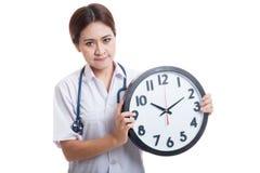 Ματαιωμένος νέος ασιατικός θηλυκός γιατρός με ένα ρολόι Στοκ εικόνα με δικαίωμα ελεύθερης χρήσης