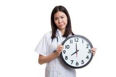Ματαιωμένος νέος ασιατικός θηλυκός γιατρός με ένα ρολόι Στοκ φωτογραφία με δικαίωμα ελεύθερης χρήσης