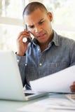 Ματαιωμένος νεαρός άνδρας στο τηλέφωνο που χρησιμοποιεί το lap-top στο σπίτι Στοκ φωτογραφία με δικαίωμα ελεύθερης χρήσης