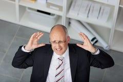Ματαιωμένος ώριμος επιχειρηματίας που αυξάνει τα όπλα στην αρχή Στοκ Εικόνες