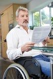 Ματαιωμένο άτομο στην αναπηρική καρέκλα που διαβάζει στο σπίτι την επιστολή στοκ φωτογραφίες