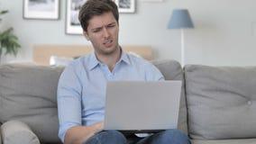 Ματαιωμένο ηλικίας άτομο που αντιδρά στην απώλεια στο lap-top καθμένος στον καναπέ φιλμ μικρού μήκους