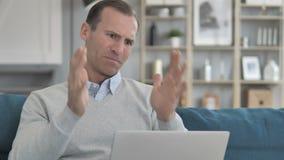 Ματαιωμένο ηλικίας άτομο που αντιδρά στην απώλεια στο lap-top καθμένος στον καναπέ απόθεμα βίντεο