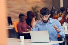 Ματαιωμένο νέο επιχειρησιακό άτομο που εργάζεται στον υπολογιστή στο σύγχρονο γραφείο ξεκινήματος Στοκ εικόνες με δικαίωμα ελεύθερης χρήσης