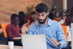 Ματαιωμένο νέο επιχειρησιακό άτομο που εργάζεται στον υπολογιστή γραφείου Στοκ Φωτογραφία