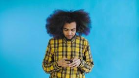 Ματαιωμένο νέο σπασμένο εκμετάλλευση κινητό τηλέφωνο ατόμων αφροαμερικάνων στο μπλε υπόβαθρο Έννοια των συγκινήσεων απόθεμα βίντεο