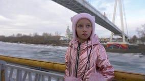 Ματαιωμένο χαμένο μικρό κορίτσι που στέκεται κοντά στα κιγκλιδώματα απόθεμα βίντεο