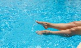 Μαυρισμένα από τον ήλιο θηλυκά πόδια, παφλασμοί, σαφές τυρκουάζ νερό λιμνών Στοκ Εικόνα