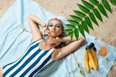 Μαυρισμένη νέα γυναίκα που παίρνει το ανθυγειινό sunbath μια θερινή ημέρα σε μια παραλία που κρύβει από τον ήλιο με το καπέλο αχύ Στοκ φωτογραφία με δικαίωμα ελεύθερης χρήσης