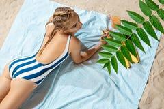 Μαυρισμένη νέα γυναίκα που παίρνει το ανθυγειινό sunbath μια θερινή ημέρα σε μια παραλία που κρύβει από τον ήλιο με το καπέλο αχύ Στοκ εικόνα με δικαίωμα ελεύθερης χρήσης