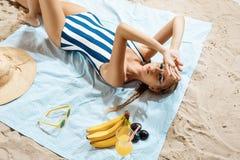 Μαυρισμένη νέα γυναίκα που παίρνει το ανθυγειινό sunbath μια θερινή ημέρα σε μια παραλία που κρύβει από τον ήλιο με το καπέλο αχύ Στοκ Εικόνες