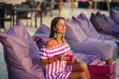 Μαυρισμένη όμορφη γυναίκα που στηρίζεται στους καναπέδες παραλιών και που πίνει ένα κοκτέιλ Το κορίτσι χαμογελά και απολαμβάνει τ στοκ εικόνες
