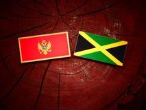 Μαυροβούνια σημαία με την τζαμαϊκανή σημαία σε ένα κολόβωμα δέντρων Στοκ φωτογραφία με δικαίωμα ελεύθερης χρήσης