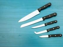 Μαχαίρια κουζινών ανοξείδωτου που τίθενται στη λεκιασμένη ξύλινη επιφάνεια Στοκ εικόνες με δικαίωμα ελεύθερης χρήσης