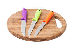 Μαχαίρια κουζινών με τις ζωηρόχρωμες πλαστικές λαβές σε έναν ξύλινο πίνακα Στοκ φωτογραφίες με δικαίωμα ελεύθερης χρήσης
