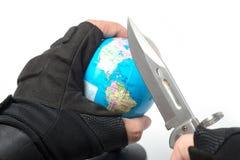 Μαχαίρι εκμετάλλευσης χεριών έτοιμο να διαπεράσει τον παγκόσμιο χάρτη σφαιρών Στοκ φωτογραφία με δικαίωμα ελεύθερης χρήσης
