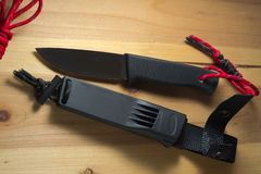 Μαχαίρι επιβίωσης με ένα κόκκινο paracord στη λαβή στοκ εικόνες