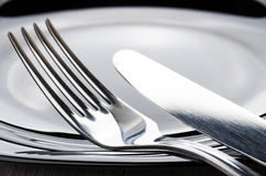Μαχαίρι δικράνων και πινάκων στην άκρη του κενού πιάτου Στοκ εικόνα με δικαίωμα ελεύθερης χρήσης