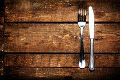 Μαχαίρι και δίκρανο πέρα από τον ξύλινο πίνακα με το διάστημα αντιγράφων Τρόφιμα διατροφής συμπυκνωμένα Στοκ εικόνες με δικαίωμα ελεύθερης χρήσης