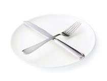 Μαχαίρι και δίκρανο πέρα από το πιάτο που απομονώνεται Στοκ Εικόνες