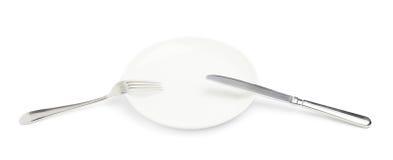Μαχαίρι και δίκρανο πέρα από το πιάτο που απομονώνεται Στοκ Φωτογραφία