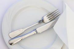 Μαχαίρι και δίκρανο στο πιάτο με την άσπρη πετσέτα Στοκ Εικόνα
