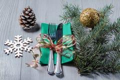 Μαχαίρι και δίκρανο στην πράσινη πετσέτα με διακοσμητικό snowflake, κώνος, Στοκ Εικόνες