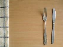 Μαχαίρι και δίκρανο στον πίνακα κοντά στην πετσέτα Στοκ Εικόνες
