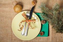 Μαχαίρι και δίκρανο στο άσπρο πιάτο και την πράσινη πετσέτα, κώνοι, glitterin Στοκ εικόνες με δικαίωμα ελεύθερης χρήσης
