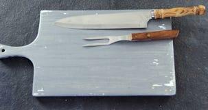 Μαχαίρι κινηματογραφήσεων σε πρώτο πλάνο, δίκρανο και ξύλινος πίνακας απόθεμα βίντεο