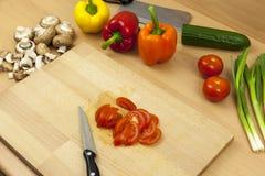 Μαχαίρι που βάζει δίπλα σε μια πρόσφατα τεμαχισμένη ντομάτα σαλάτας Στοκ Εικόνα