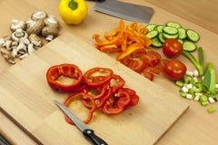 Μαχαίρι που βάζει πάνω από ένα πρόσφατα κομμένο δαχτυλίδι κόκκινο πιπέρι κουδουνιών Στοκ Φωτογραφίες
