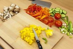 Μαχαίρι που βάζει πάνω από ένα πρόσφατα χωρισμένο σε τετράγωνα κίτρινο πιπέρι κουδουνιών Στοκ Εικόνες