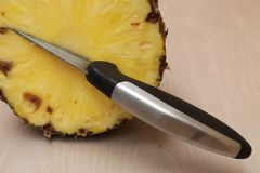Μαχαίρι που κολλιέται σε ένα κομμάτι περικοπών ενός ανανά Στοκ εικόνα με δικαίωμα ελεύθερης χρήσης