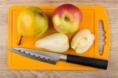Μαχαίρι της Apple, αχλαδιών και κουζινών στον τέμνοντα πίνακα Στοκ Φωτογραφίες