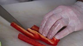 Μαχαίρι του μάγειρα κινηματογραφήσεων σε πρώτο πλάνο που τεμαχίζει το juicy κόκκινο πιπέρι, που μαγειρεύει τη διαδικασία απόθεμα βίντεο