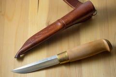 Μαχαίρι χειροποίητο με ένα ξύλινο μαχαίρι λαβών στο καφετί θηκάρι δέρματος στοκ φωτογραφία