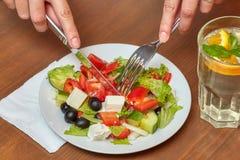 μαχαίρι χεριών δικράνων Σαλάτα και ποτό στον πίνακα Στοκ Εικόνες