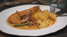 Μαχαιροπήρουνα κινηματογραφήσεων σε πρώτο πλάνο με το εύγευστο γεύμα θαλασσινών στο εστιατόριο φιλμ μικρού μήκους
