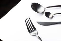 Μαχαιροπήρουνα που τίθενται με το μαύρα δίκρανο, το μαχαίρι και το κουτάλι Στοκ Φωτογραφία