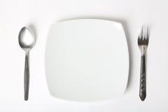 Μαχαιροπήρουνα που τίθενται με το πιάτο. Στην άσπρη ανασκόπηση Στοκ Εικόνα
