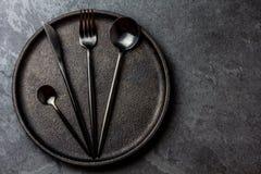 Μαχαιροπήρουνα που τίθενται στο πιάτο μαύρος πίνακας τιμής τών παρ&alp Τοπ όψη Στοκ Εικόνες