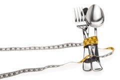 Μαχαιροπήρουνα που τυλίγονται με ένα μέτρο ταινιών, σύμβολο για μια διατροφή στοκ εικόνες