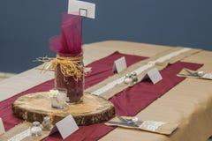 Μαχαιροπήρουνα ρύθμισης γαμήλιων πινάκων με την ξύλινα πιατέλα και το βάζο του Mason στοκ εικόνες