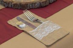 Μαχαιροπήρουνα ρύθμισης γαμήλιων πινάκων με Burgundy και το καφετί επιτραπέζιο ύφασμα στοκ εικόνες