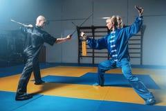 Μαχητές, άνδρας και γυναίκα Wushu με τα ξίφη Στοκ εικόνα με δικαίωμα ελεύθερης χρήσης